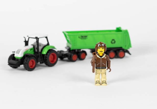 Bauer und sein Traktor im Hintergrund