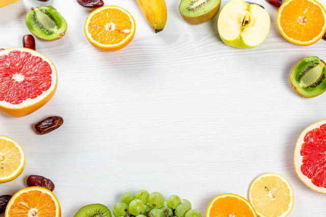 Frame with colorful fresh fruit and dried dates on white wooden background with free space in the middle