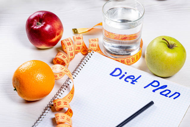 """Orange, Apple, glass of water and measuring tape near the notebook with the inscription """"diet plan"""