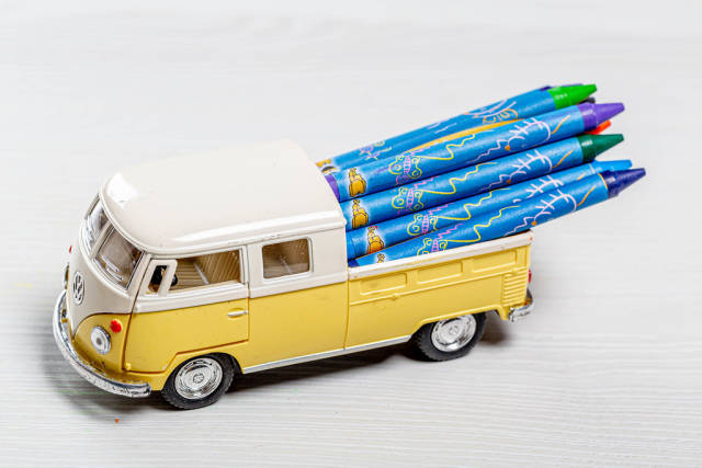 Toy car with colored pencils in the trunk. The concept of childrens time in school