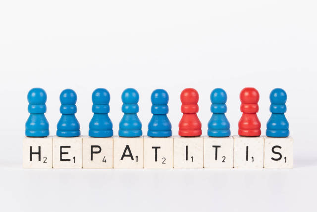 Word Hepatitis written on wooden blocks with pawns in various colors on white background