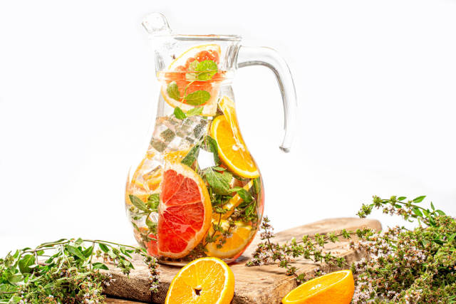 Glass jug with ice cubes, fresh mint, and citrus slices