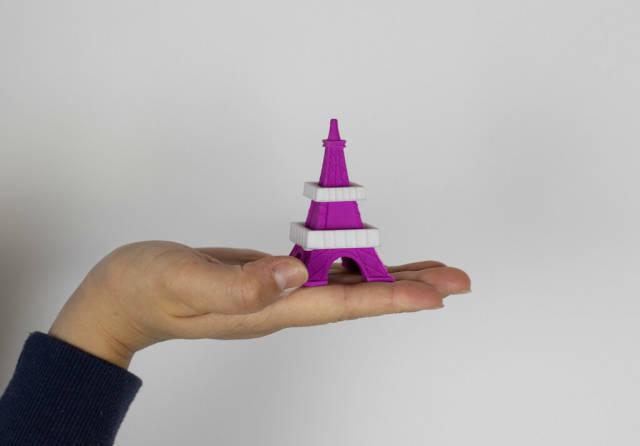 Kleines Modell des Eiffelturms in der Hand eines Mädchens