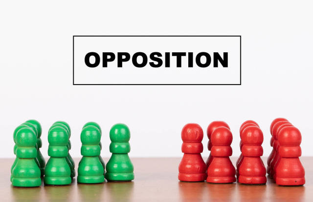 Opposition concept with pawn figurines on table