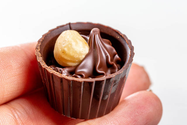 Chocolate candy with hazelnuts in a womans hand