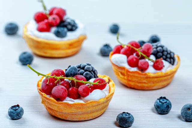 Tartlets with cream and fresh berries on a white wooden background