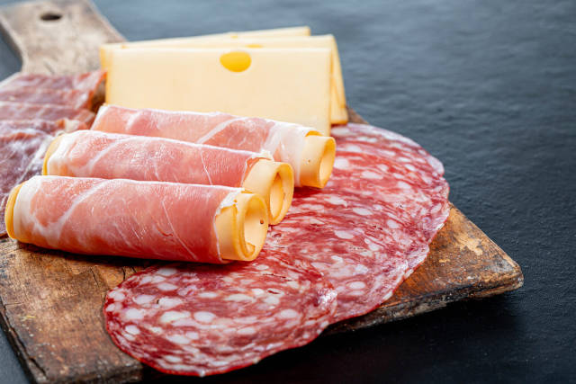 Salami, jamon, ham and cheese sliced on old kitchen wooden Board