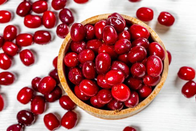 Fresh cornel berries in a wooden bowl. Top view (Flip 2019)
