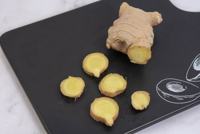 Sliced Ginger on the black tray with Tasty sign