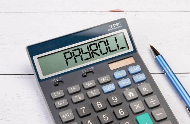 Taschenrechner zeigt das Wort Lohnabrechnung (Payroll) im Display an