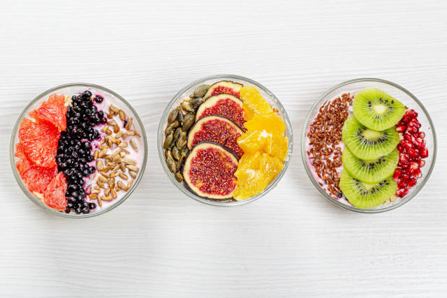 Different Breakfast options with oatmeal, fresh fruit and seeds. Top view