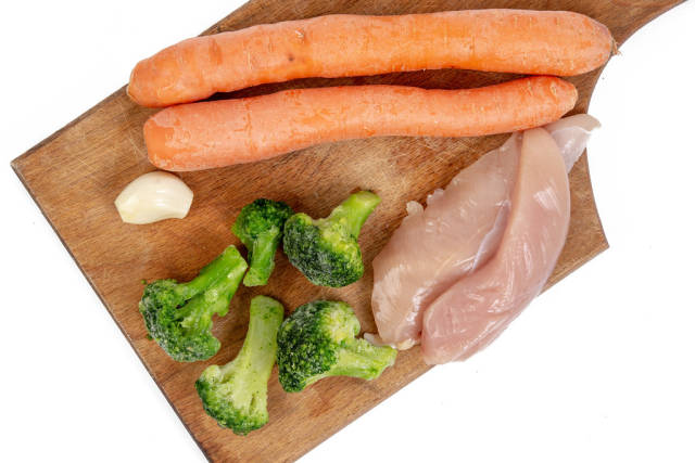 Chicken breasts with Carrots Broccoli and Garlic on the wooden board