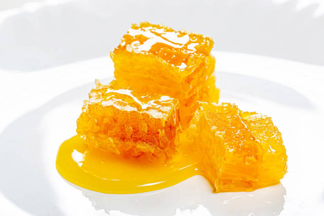 Bee honeycomb and honey on a white plate