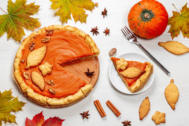 Pumpkin pie with autumn decorations on white wooden table. Top view