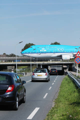 KLM B747 taxiing on the bridge over cars road at Amsterdam Airport
