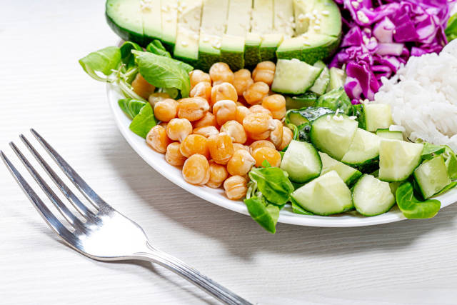 Close up of chickpeas with sliced vegetables and rice on a plate