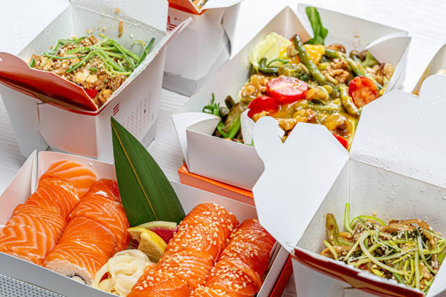 Chinese food in cardboard boxes-salad, sushi, noodles, rice