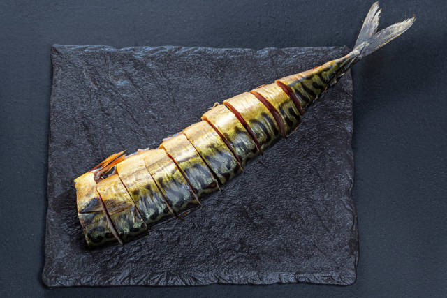 Top view sliced pieces of smoked mackerel on a black background