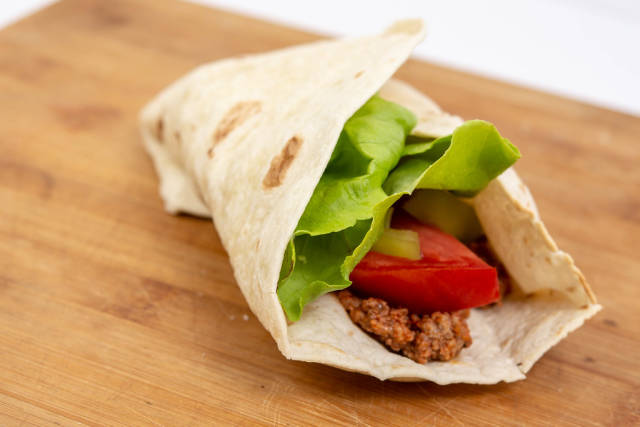 Tortilla with Minced meat Tomato and Lettuce on the wooden table