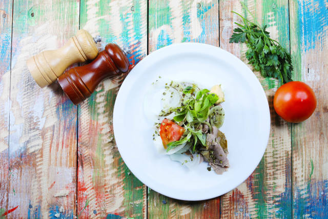 Pork steak with fresh tomato in white plate. Wooden vintage background
