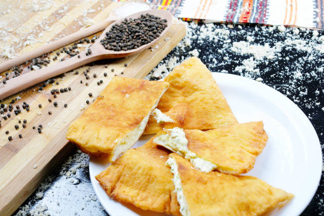 Langos with cheese, Hungarian traditional recipe. Black background