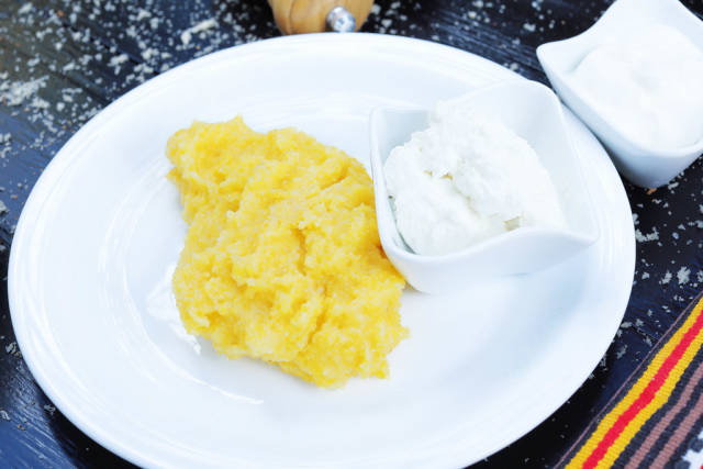 Polenta with cream on a white plate. Balkan traditional recipe