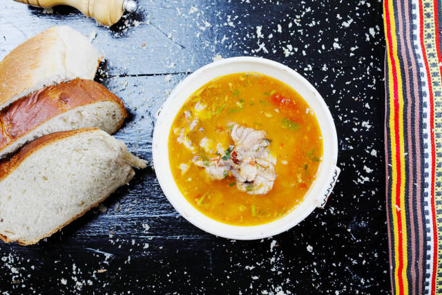 Fish soup served with homemade bread, black background