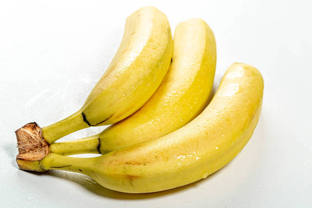 A branch of fresh ripe bananas on a white background