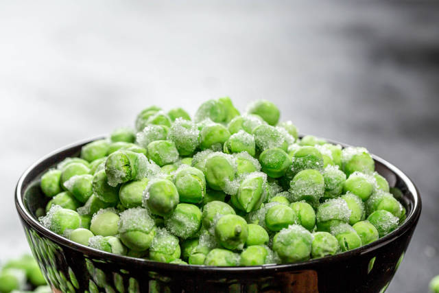 Frozen green peas in a bowl closeup