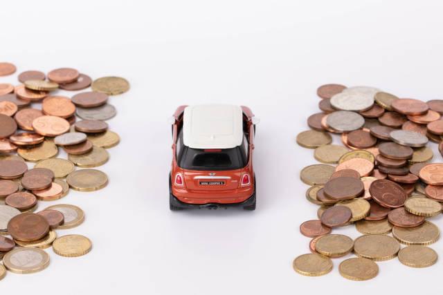 Red car driving inbetween coins