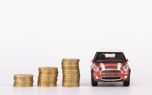 Stacks of coins with car on white background