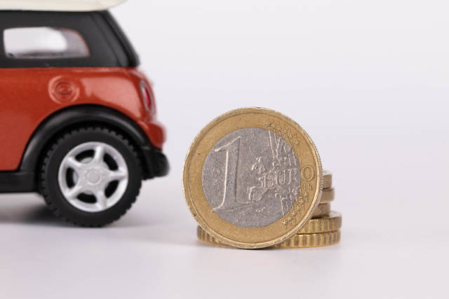 Car with one Euro coin on white background