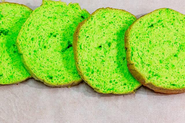 Green sliced sponge biscuit on parchment paper