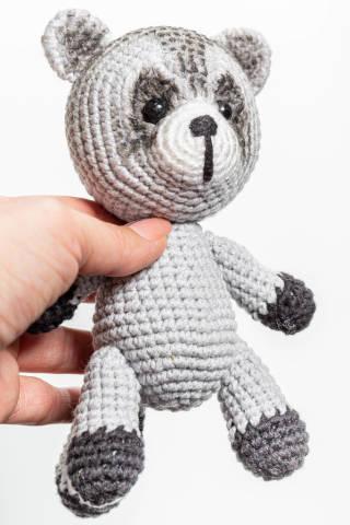 Crochet toy raccoon in hand closeup