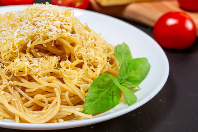 Spaghetti with grated cheese and sesame seeds close-up