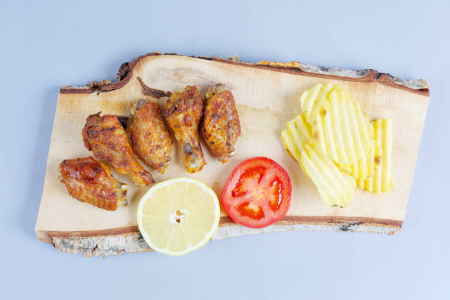 Chicken wings with potato chips on a wooden chopper