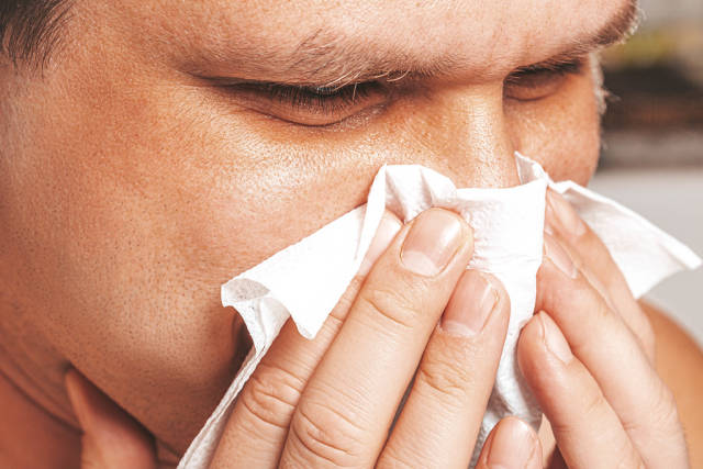 Close-up of a man with a runny nose holding a napkin near his nose
