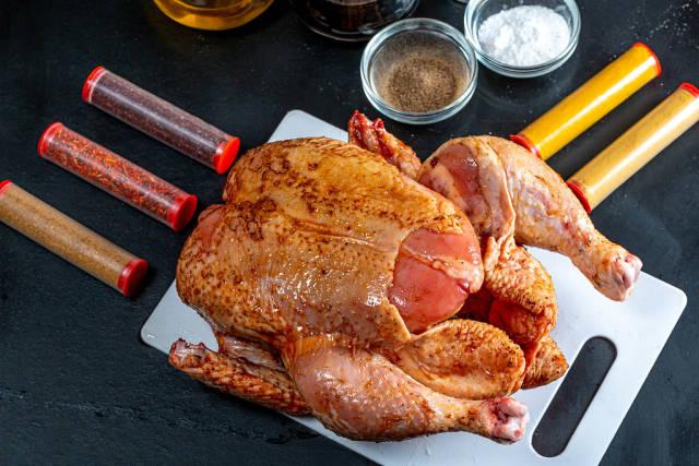 Raw chicken with natural spices on dark background