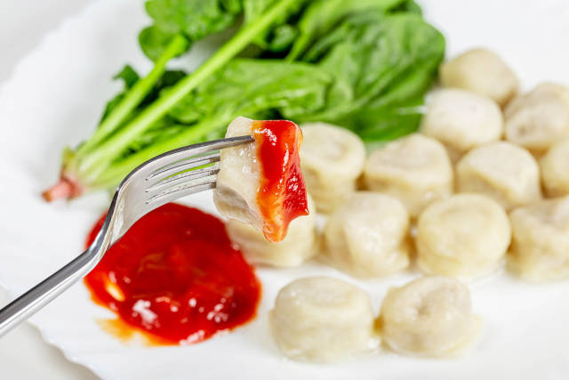 Close up vegetarian dumplings with spinach and tomato sauce on a fork