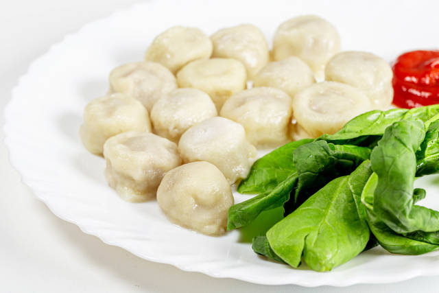 Boiled dumplings with spinach and tomato sauce