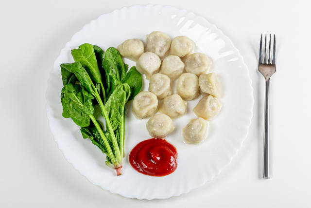 Top view dumplings with spinach and tomato sauce