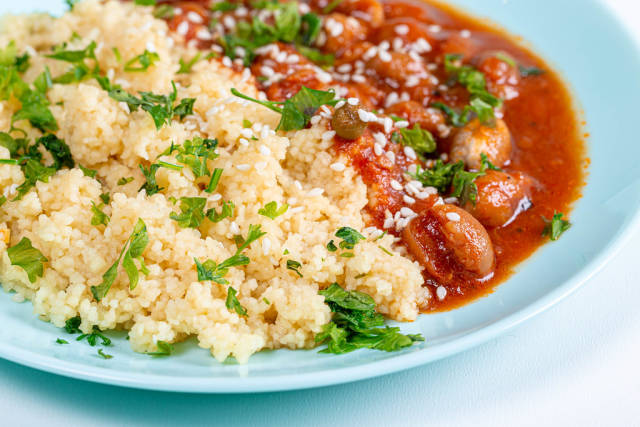 Closeup cereal couscous with spacely in tomato sauce and sesame seeds