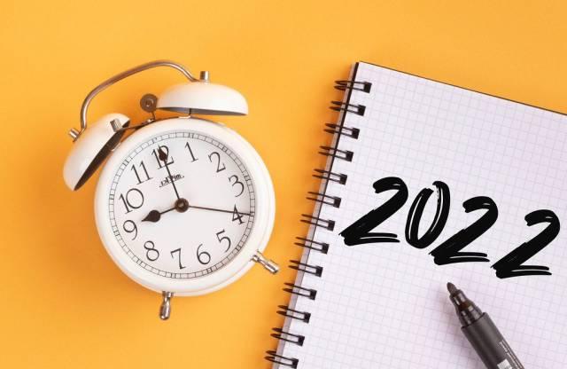 Wecker und ein Heft mit '2022' Text mit einem Filzstift drauf vor gelbem Hintergrund