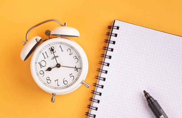 White alarm clock on yellow background with empty notepad