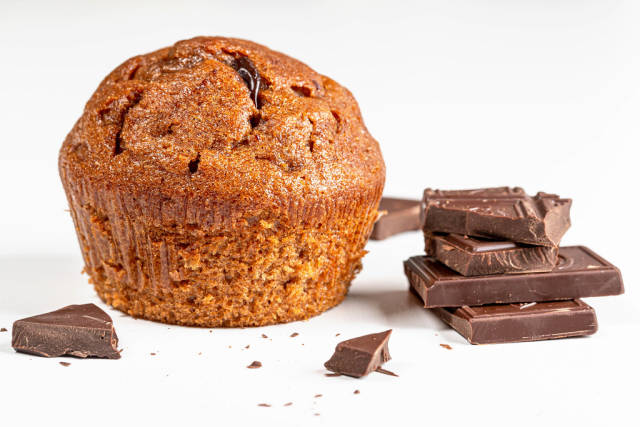 Brown muffin with chocolate pieces on white background