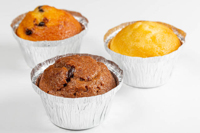 Three muffins with different fillings on a white background