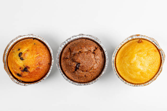 Top view of chocolate, caramel and vanilla muffins on white background