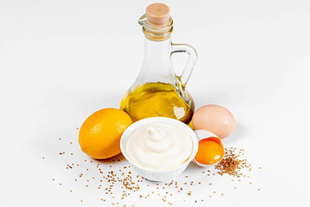 Fresh mayonnaise with ingredients on a white background