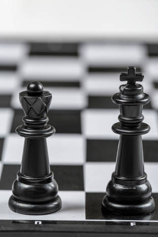 Black king and Queen chess pieces stand on a chessboard
