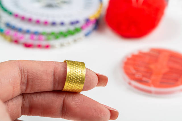 Close-up of a thimble for sewing on a womans finger